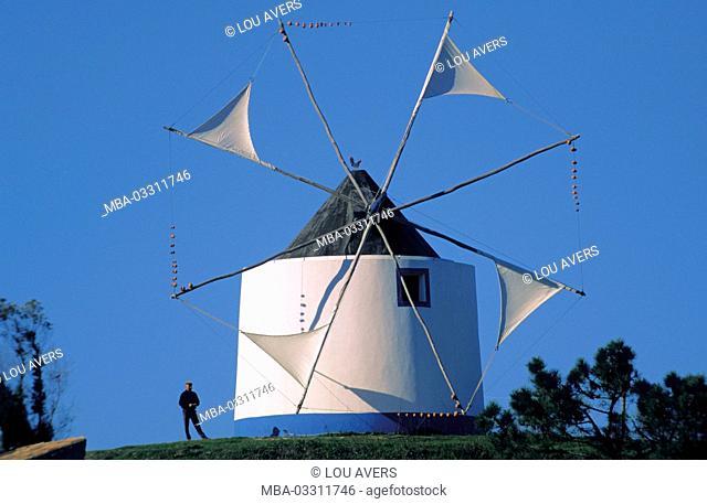 Portugal, Algarve, Müller Alexandre Candeias beside historical windmill of Odeceixe
