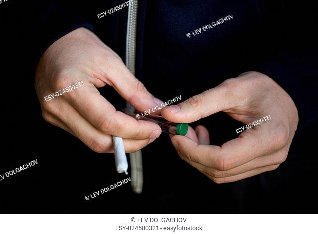 drug use, substance abuse, addiction, people and smoking concept - close up of addict hands with marijuana joint and blunt tube