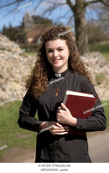 Young vicar walking around her country parish