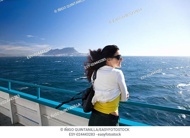 woman, white and yellow clothes, leaning on boat railing in ferry in Mediterranean sea Strait of Gibraltar with the Rock in the background, in Cadiz, Andalusia