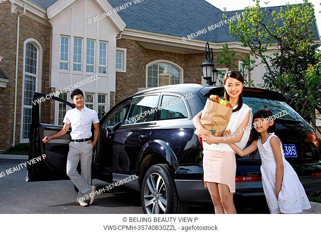 Oriental family standing be car holding food