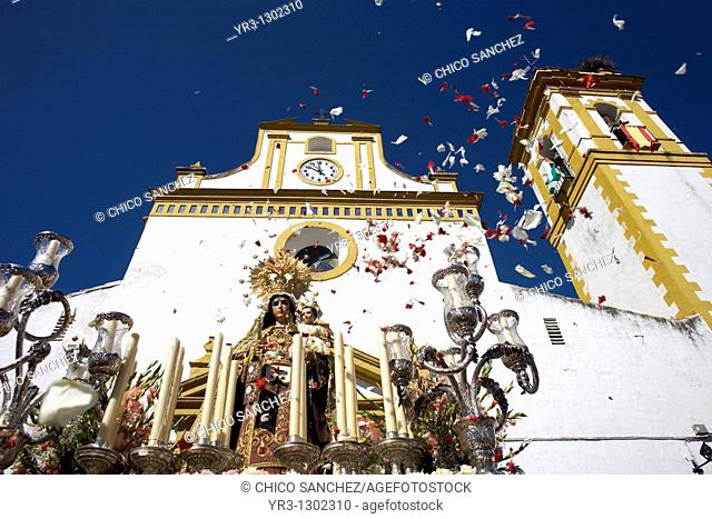 People throw flowers petals toward a wooden statue of the Virgin Carmen is publicly displayed during a Holy Week procession in the town of Prado del Rey in...