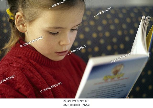 A little girl, 5-10 years old, reading a book