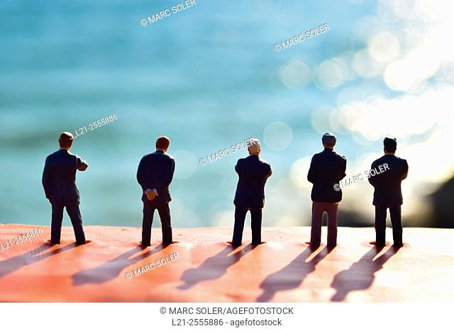 Figurines of businessmen watching a blurred landscape. Toy businessmen team, silhouettes of men against blurred sea
