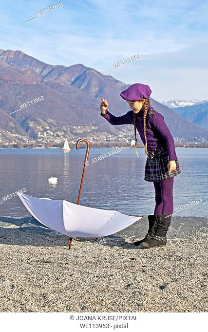 Girl is turning an umbrella at the shore of the Lake Maggiore