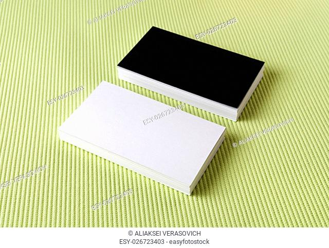 Several black and white business cards on a green background