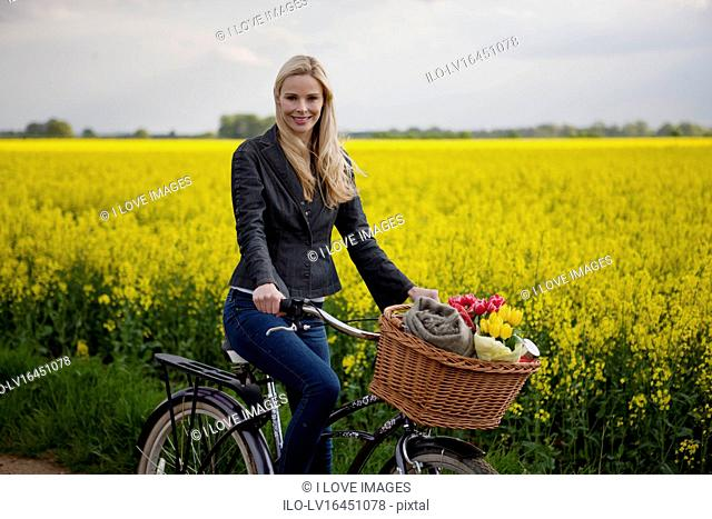 A young woman riding a bicycle next to a rape seed field in flower