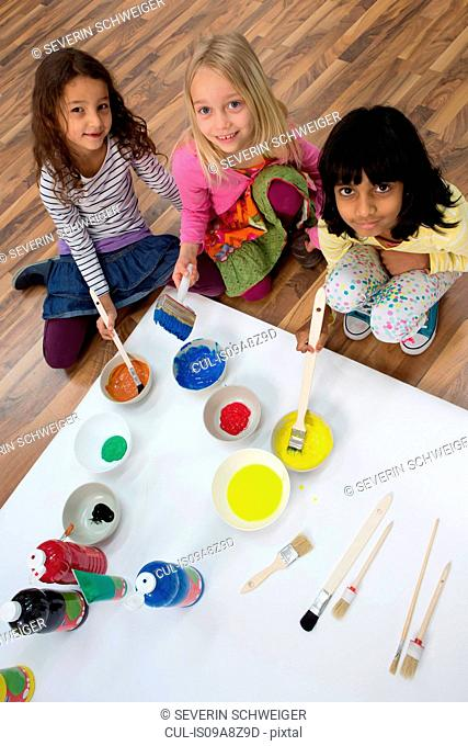 Portrait of three girls painting on floor