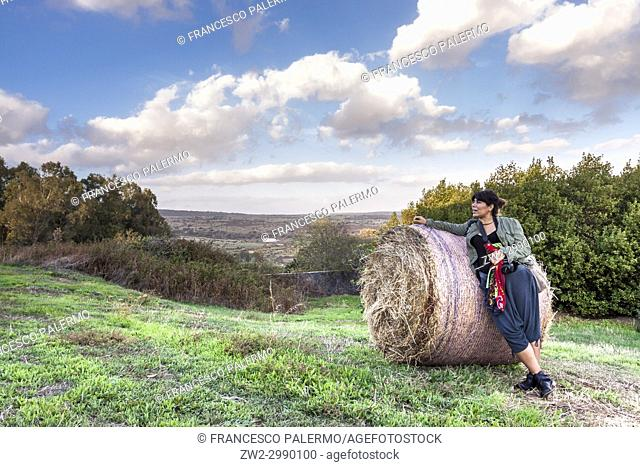 Front view of woman leaning on hay bale at field against dramatic sky. Bonarcado, Sardinia. Italy
