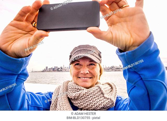 Woman taking picture by city skyline, San Francisco, California, United States