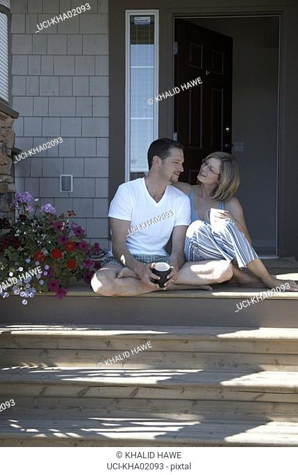 Young couple sitting on doorstep