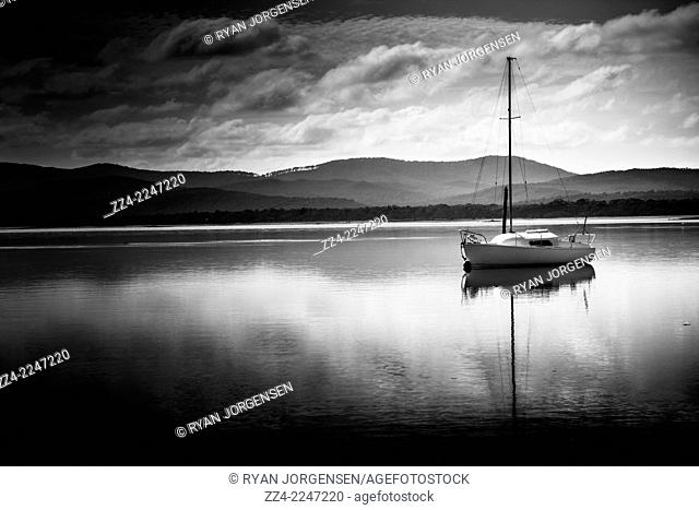 Black and white holiday landscape of a yacht sailing boat with sails down parked in Port Sorell bay at nightfall. Taken Tasmania, Australia