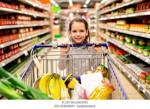 sale, consumerism and people concept - happy little girl with food in shopping cart at grocery store