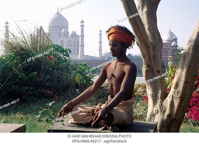 man sitting in yoga posture near at Taj mahal Seventh Wonder of The World ; Agra ; Uttar Pradesh ; India