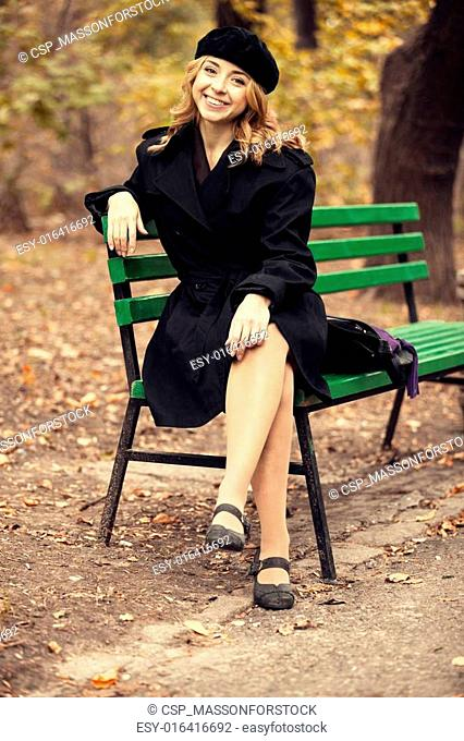 Style redhead girl sitting at bench in autumn park