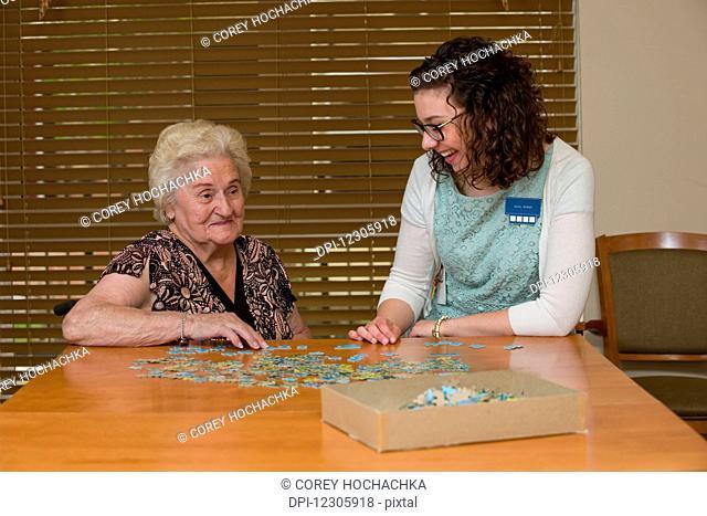 Senior citizen and caregiver building a puzzle; Edmonton, Alberta, Canada