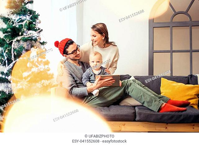 lovely family sharing digital tablet near the wood stove on a winter evening, enjoying the warm Christmas atmosphere in their living room