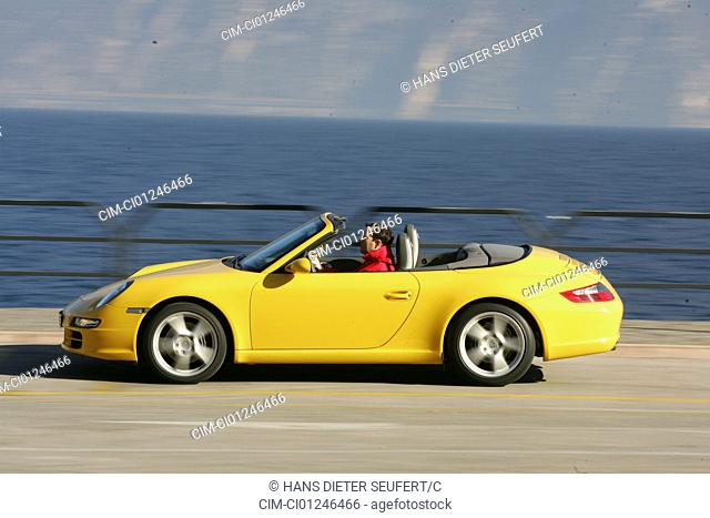 Car, Porsche 911 Carrera Convertible, model year 2005-, yellow, driving, side view, open top, country road