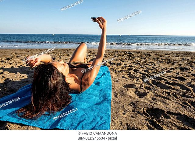 Caucasian woman laying on blanket on beach posing for cell phone selfie