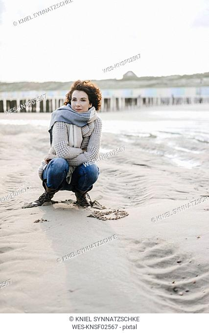 Woman crouching on the beach