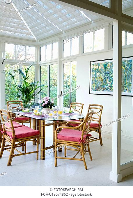 Cane chairs with red cushions in Marston + Langinger conservatory dining room with white ceramic floor tiles