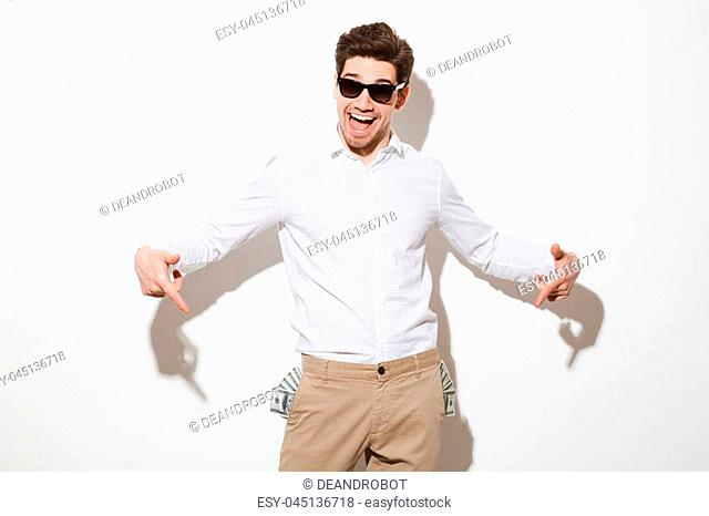 Portrait of a happy young man pointing fingers at money banknotes in his pockets isolated over white background