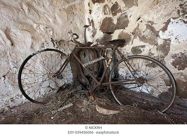 An old rusty bicycle propped up in the corner of an old stone shed