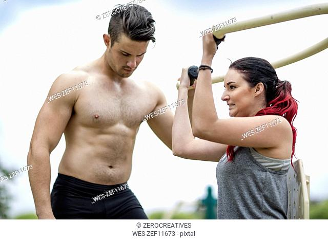 Young men and woman doing strength training in park