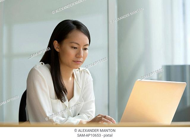 Singapore, Mid adult woman using laptop
