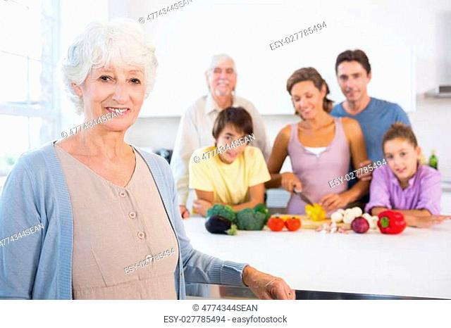 Grandmother standing beside kitchen counter with family behind her