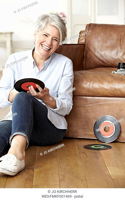 Mature woman sitting on floor holding record