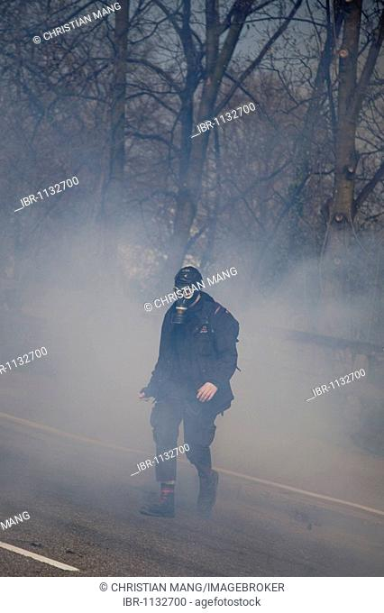 Protester running through fog of teargas during protests against NATO-summit, Strasbourg, France