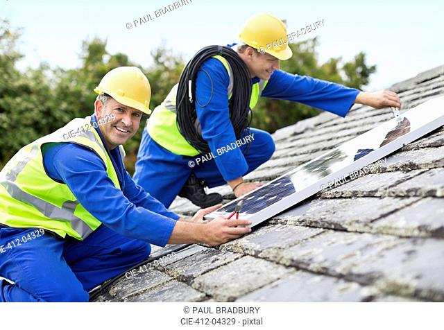 Workers installing solar panels on roof