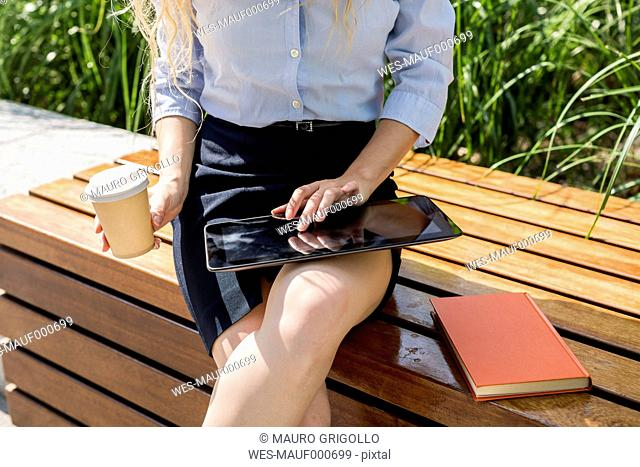 Businesswoman sitting on bench using digital tablet