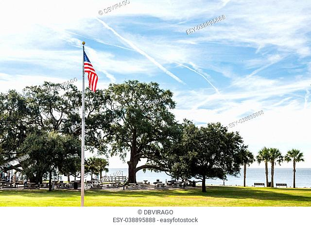 An American flag in a public park with grass and trees on the coast