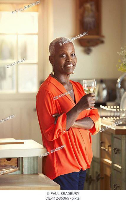 Portrait smiling senior woman drinking wine in kitchen