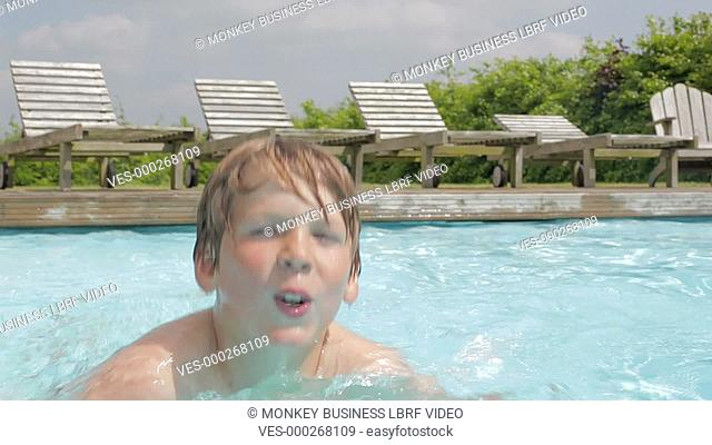 Camera tracks young boy as he swims in outdoor pool.Shot on Canon 5D Mk2 at a frame rate of 25fps