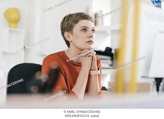 Woman at desk in office looking at computer screen