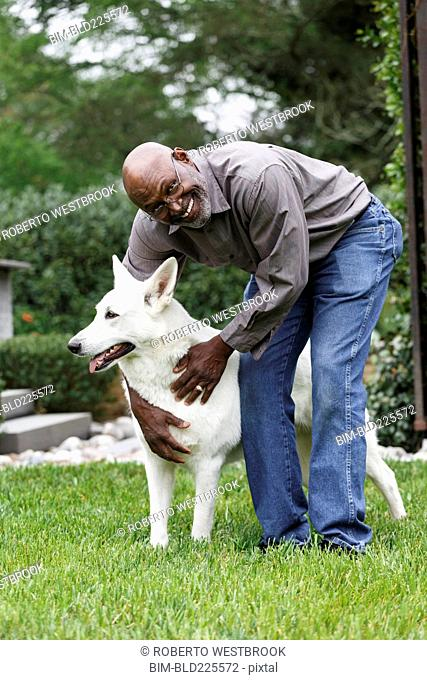 Black man petting white dog in backyard
