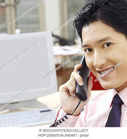 Portrait of a businessman talking on the telephone and smiling