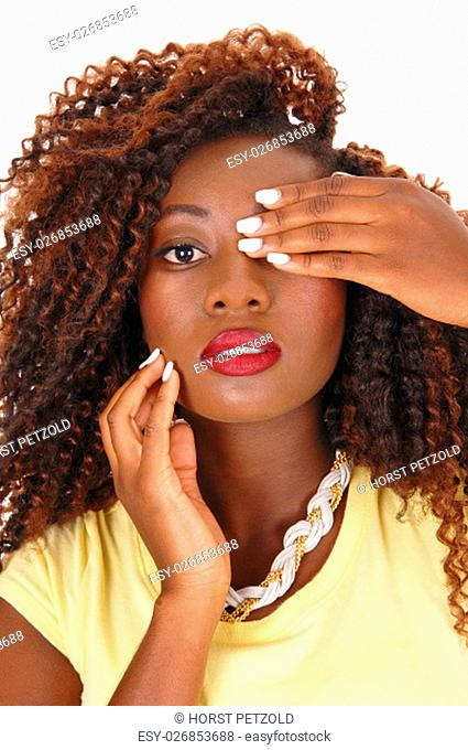 A beautiful African American woman with wild hair hold one hand over .her eye, closeup isolated for white background.