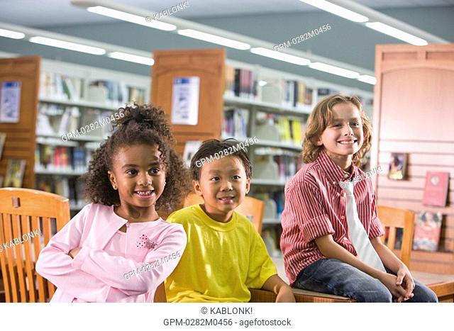 Three elementary school children smiling in school library