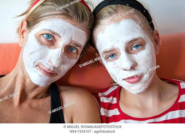 Young mother with her daughter at the time of relaxation  Using the free time for personal care  Using a facial mask to clean skin of the face