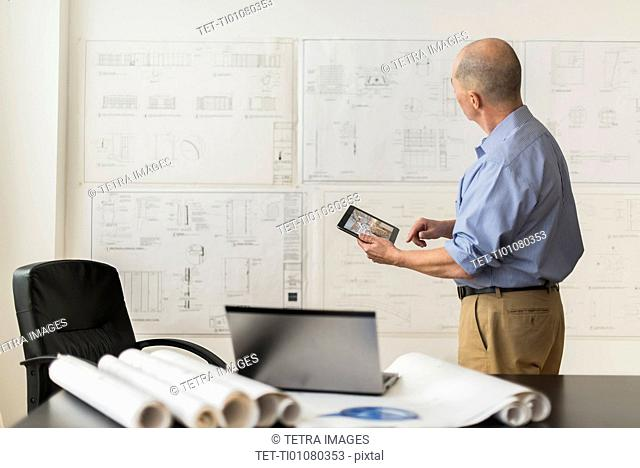 Mature architect looking at blueprints in office