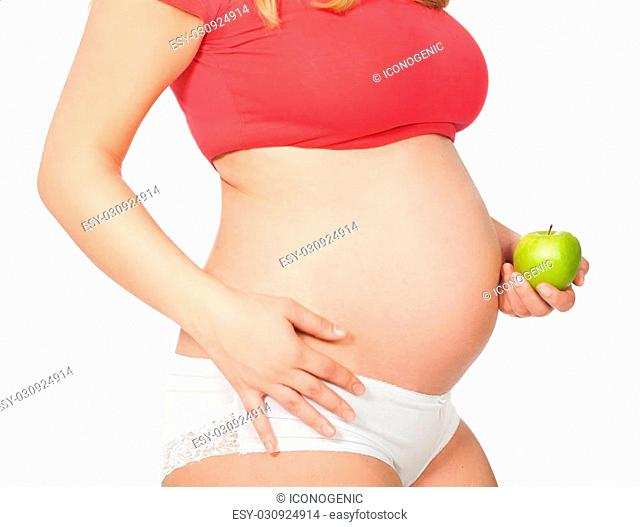 Torso of a pregnant woman with green apple