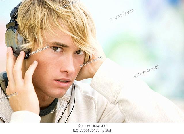 Portrait of a young man listening to music in front of a graffiti covered wall