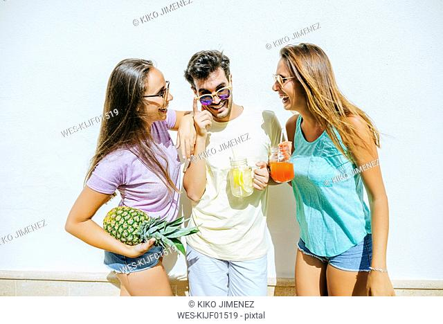 Happy friends holding refreshing drinks and pineapple in front of white wall