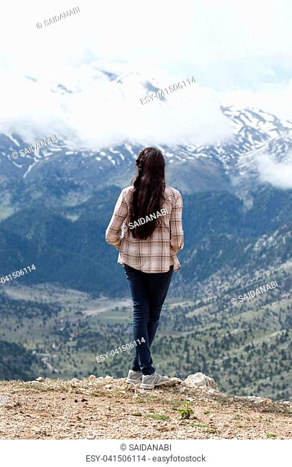 Vertical Full lenght backview portrait of traveller brunette woman with long straight hair wearing checked shirt and jeans enjoying picturesque panoramic view...