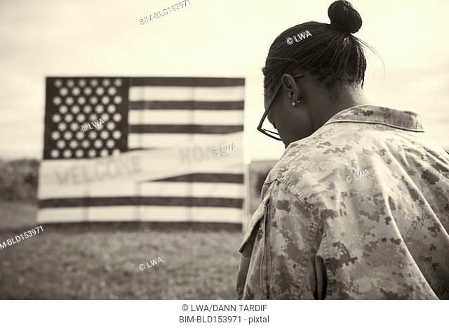 Returning Black soldier admiring American flag welcome home sign