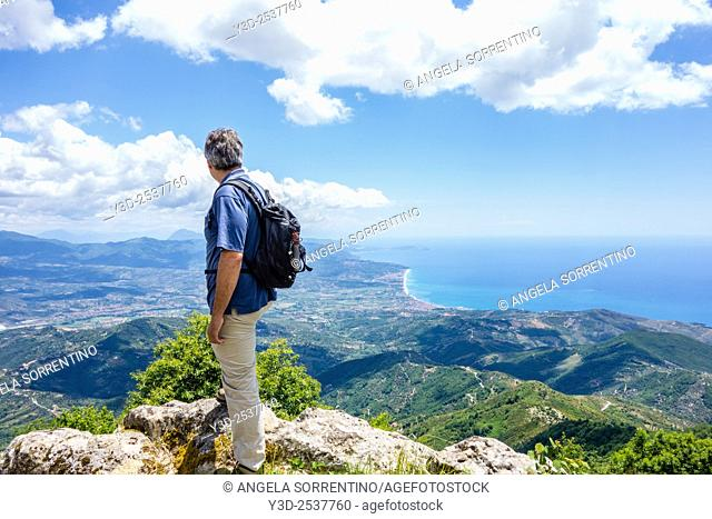 Mature man admiring stunning view of Cilento coastline from the top of a mountain